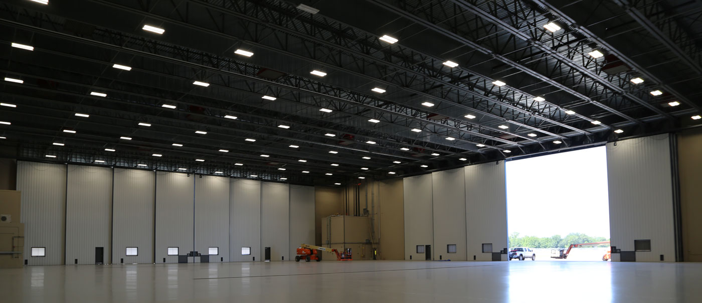 large airplane hangar with bottom rolling doors