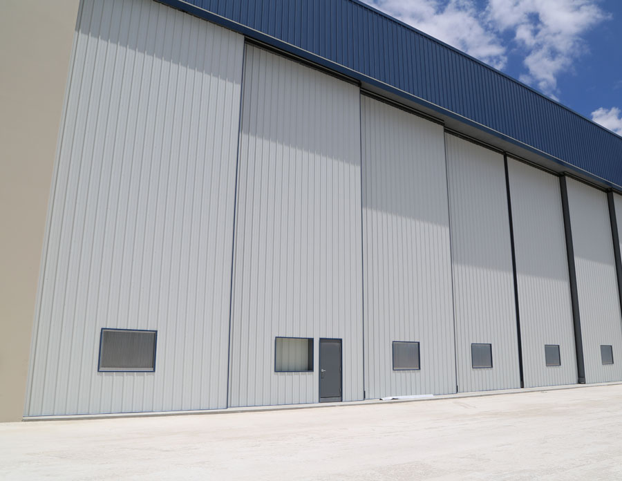 Aircraft hangar doors bottom rolling bi fold single
